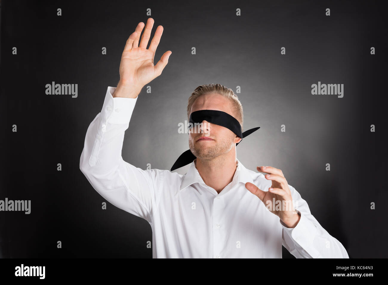 Giovani bendati imprenditore confuso contro uno sfondo grigio Immagini Stock