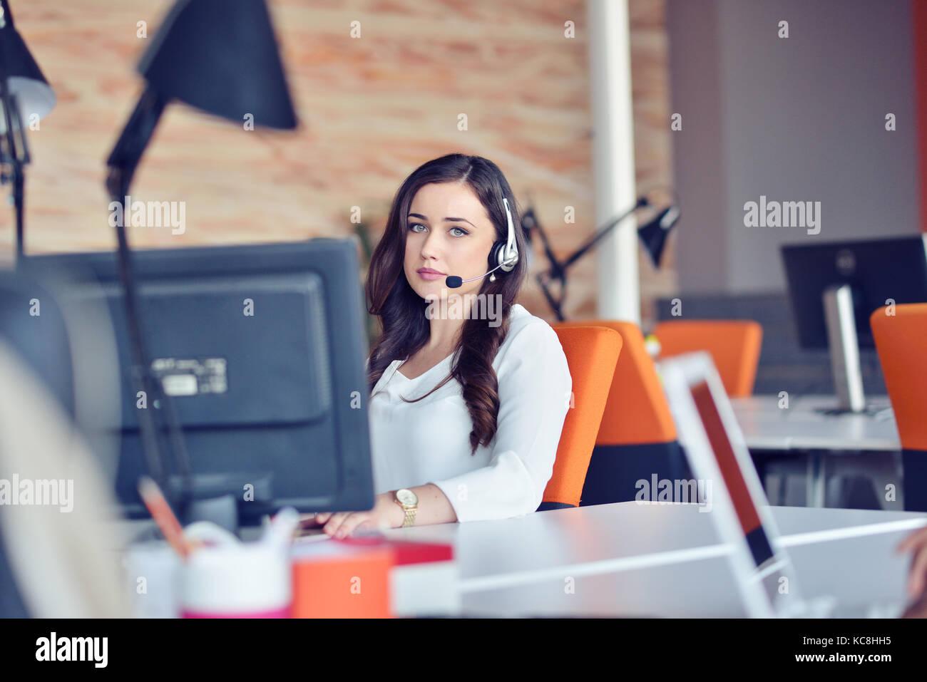 Giovane donna che lavorano nei call center, circondato da colleghi Immagini Stock