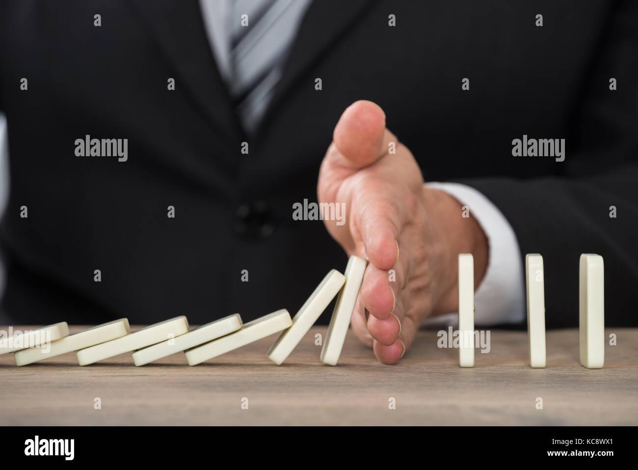 Close-up di un imprenditore mano domino di arresto di cadere su una scrivania in ufficio Immagini Stock