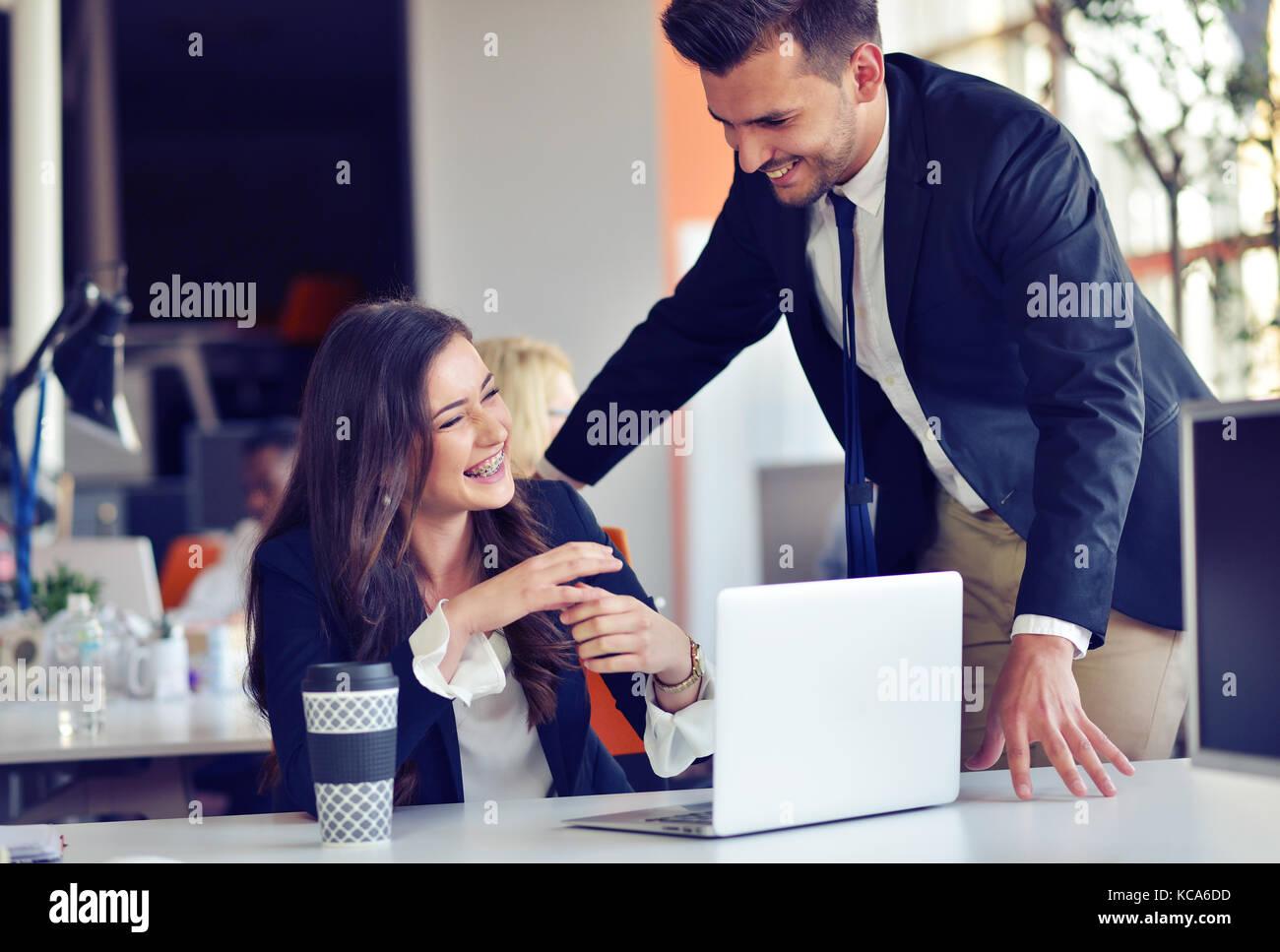 Startup business concetto con giovane coppia multietnica in ufficio moderno lavorando sul computer portatile Immagini Stock