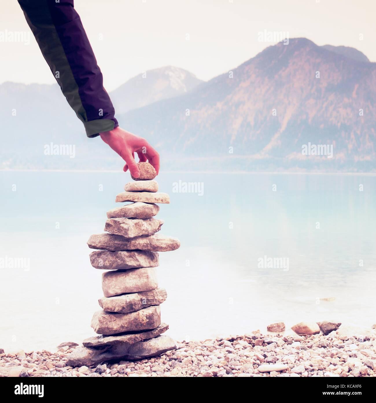 Uomo piramide costruito da ciottoli. equilibrata piramide di pietra sulla riva delle acque blu del lago di montagna. Immagini Stock
