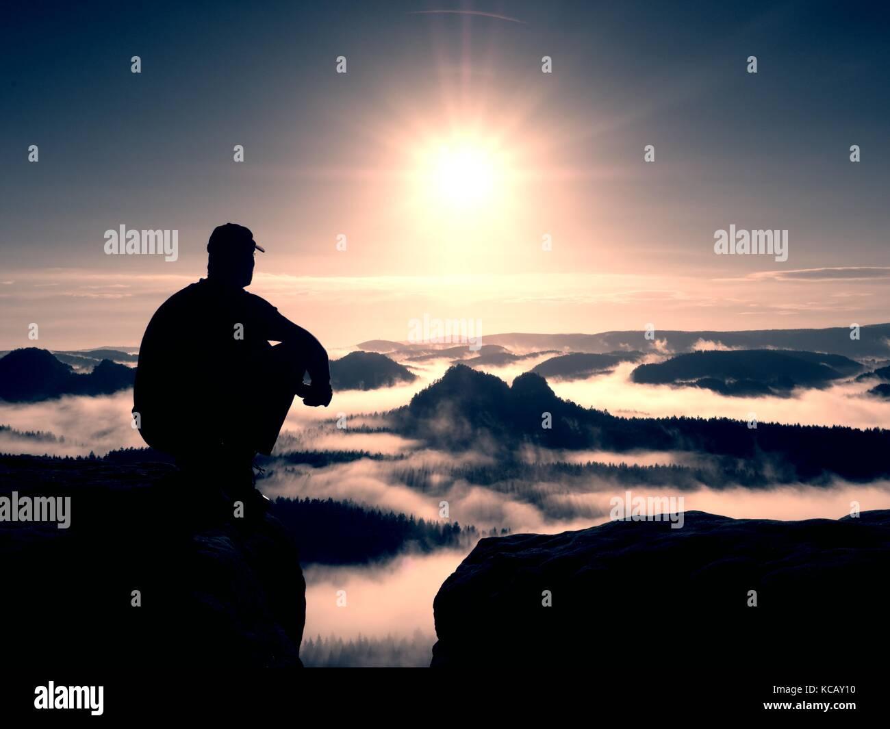 Momento di solitudine. l uomo con cappuccio sedersi sul picco di roccia e guardare nella nebbia colorata e la nebbia Immagini Stock