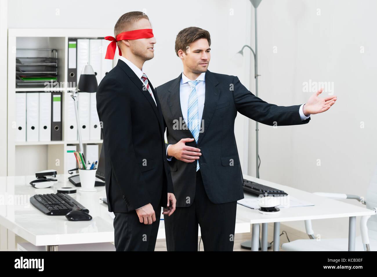 Fiducioso giovane impreditore assistere gli occhi bendati partner in ufficio Immagini Stock