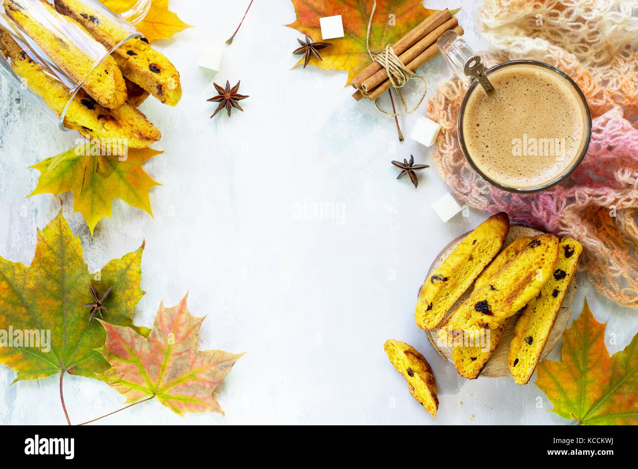 Pane appena sfornato uvetta e cannella biscotti e una tazza di caffè cappuccino su una cucina un tavolo di Immagini Stock