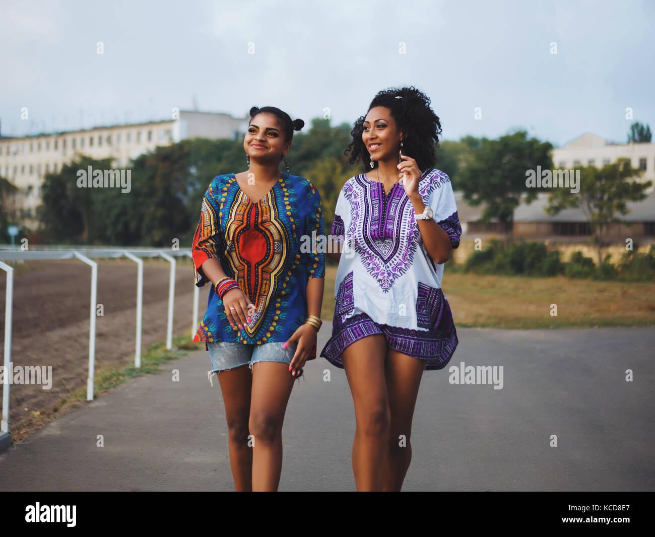 Due belle felice afro-americane donne amici passeggiate all aperto. giovani  razza mista le ragazze che indossano vestiti colorati comunica d45d68a9041