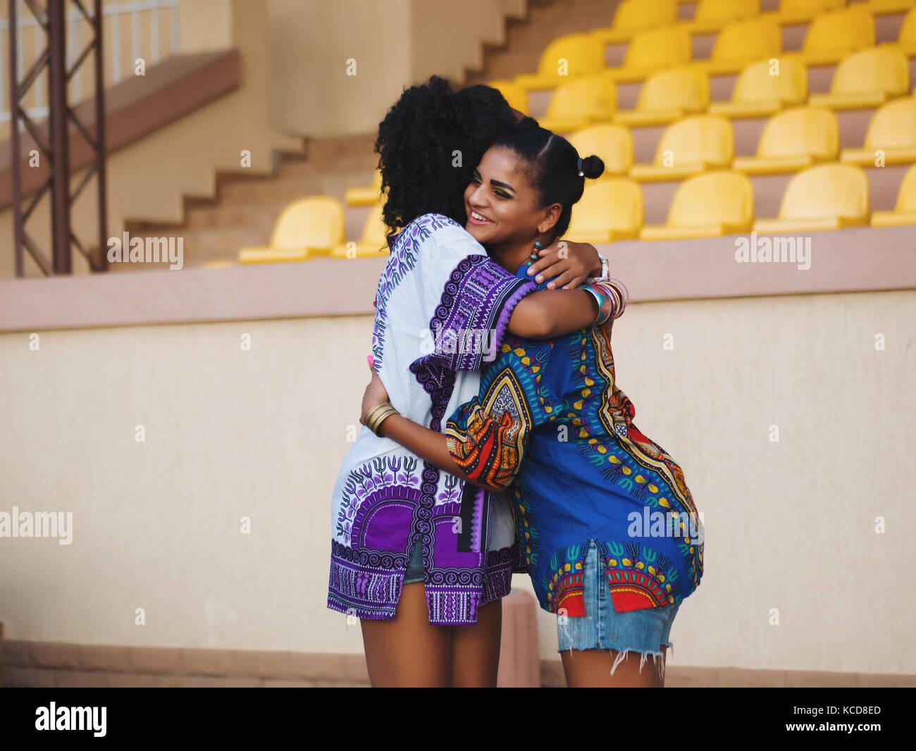 Due belle felice afro-americane donne amici abbraccia ogni altra outdoor.  giovani razza mista le ragazze che indossano vestiti colorati comunica fa07d4a53d7