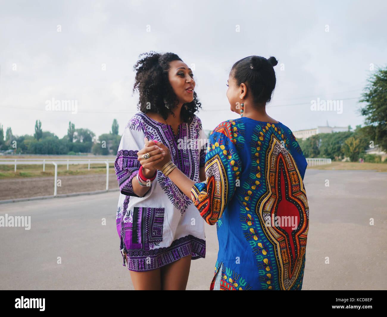 Due belle felice afro-americane donne amici outdoor permanente. giovani  razza mista le ragazze che indossano vestiti colorati comunica 404582e0077