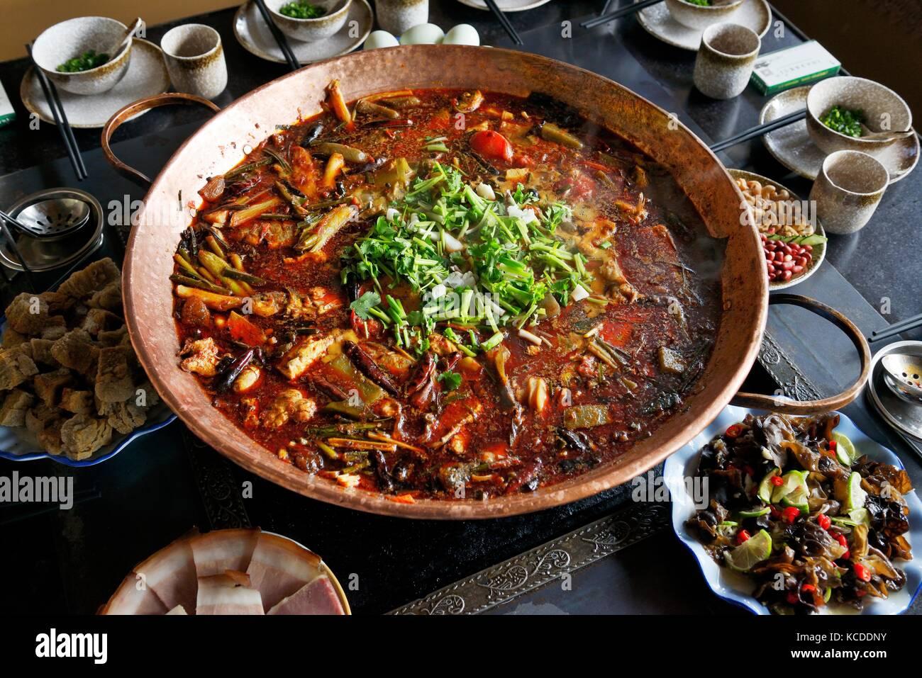 Cucina cinese tradizionale. nella provincia dello Yunnan hotpot. tipici tradizionali e di pesce piatto di vegetali di naxi gruppo etnico persone lashi sulla riva del lago, Lijang Foto Stock