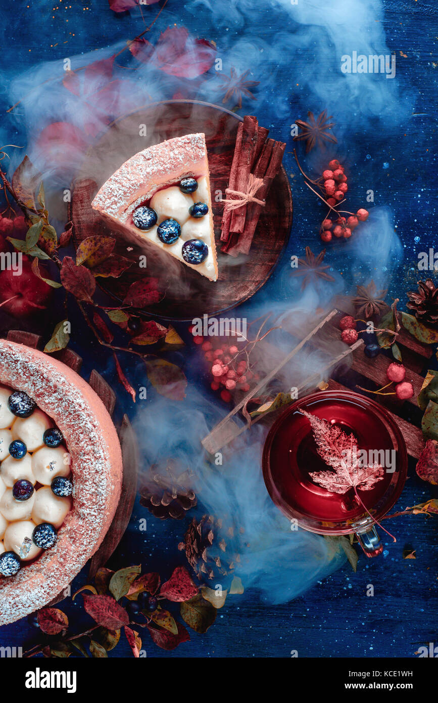 Dark autunno ancora in vita con una panna montata torta ai mirtilli, tè caldo e decorazioni floreali su uno Immagini Stock
