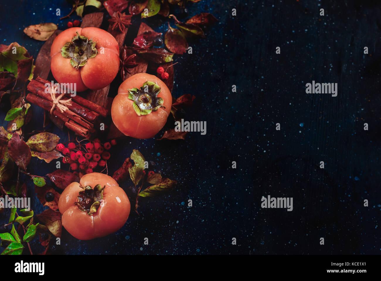 Persimmons maturi al buio su un sfondo di legno con foglie di autunno bacche e cannella. laici piatta con copia Immagini Stock