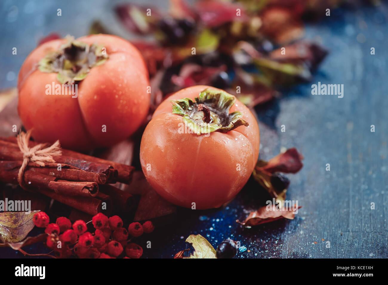 Persimmons maturi al buio su un sfondo di legno con foglie di autunno bacche e cannella. laici piatta con copia Foto Stock
