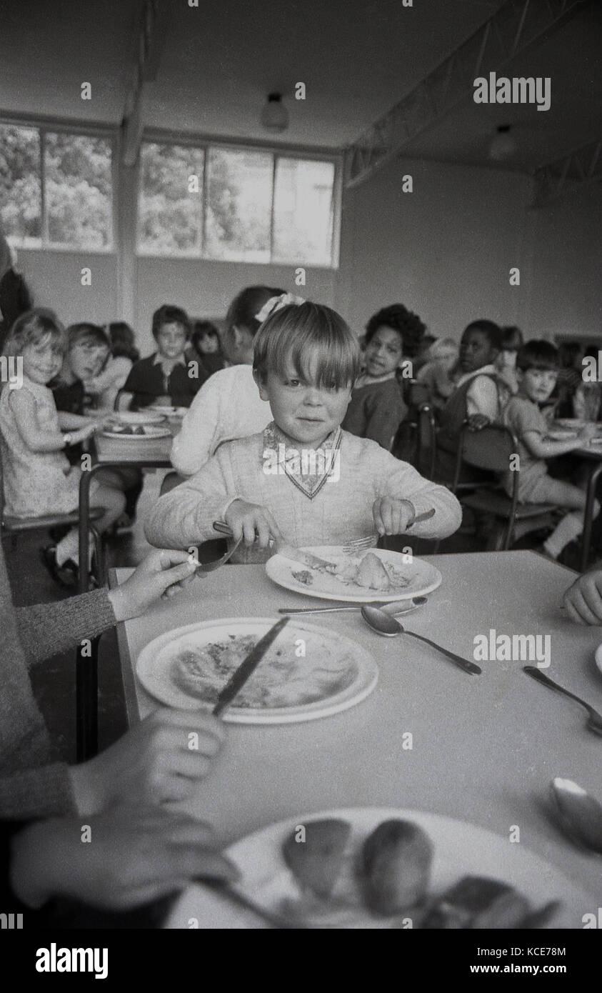 Anni Settanta, storico, immagine mostra un giovane ragazzo seduto a mangiare la sua scuola cena ad un tavolo con altri chldren Langbourne presso la scuola primaria. Dulwich, Londra, Inghilterra, Regno Unito. Foto Stock