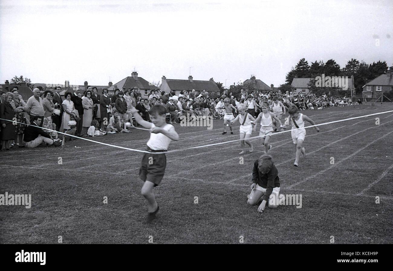 Anni sessanta, foto storiche di ragazzi che partecipano in un uovo-e-corsa col cucchiaio in una scuola primaria Immagini Stock