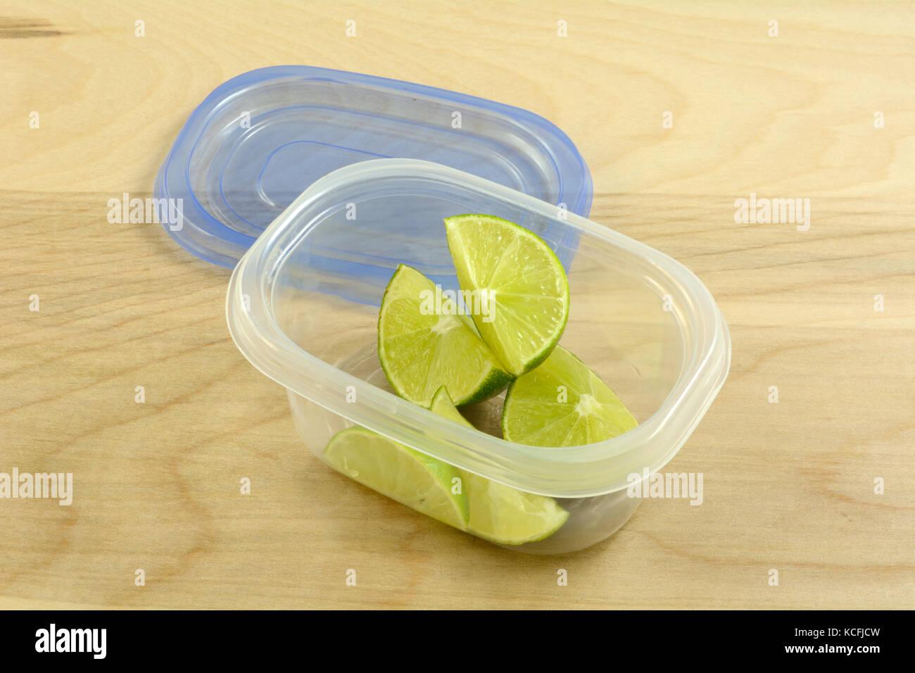 Preparare in anticipo per party con bevande o cena mettendo spicchi di lime in contenitore in plastica Immagini Stock