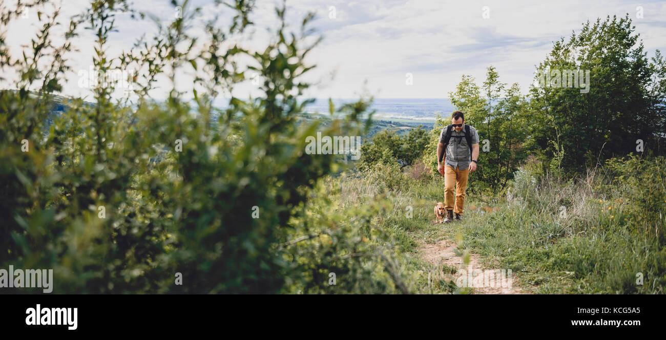 Uomo con un cane a piedi lungo un sentiero escursionistico sulla montagna Immagini Stock