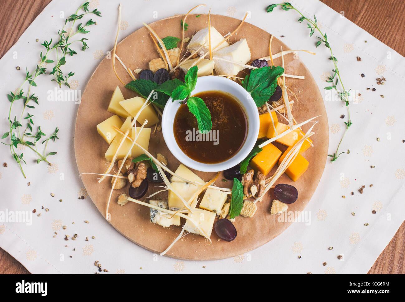 Diversi tipi di formaggio con miele, frutta a guscio e frutta sulla rotonda di legno Immagini Stock