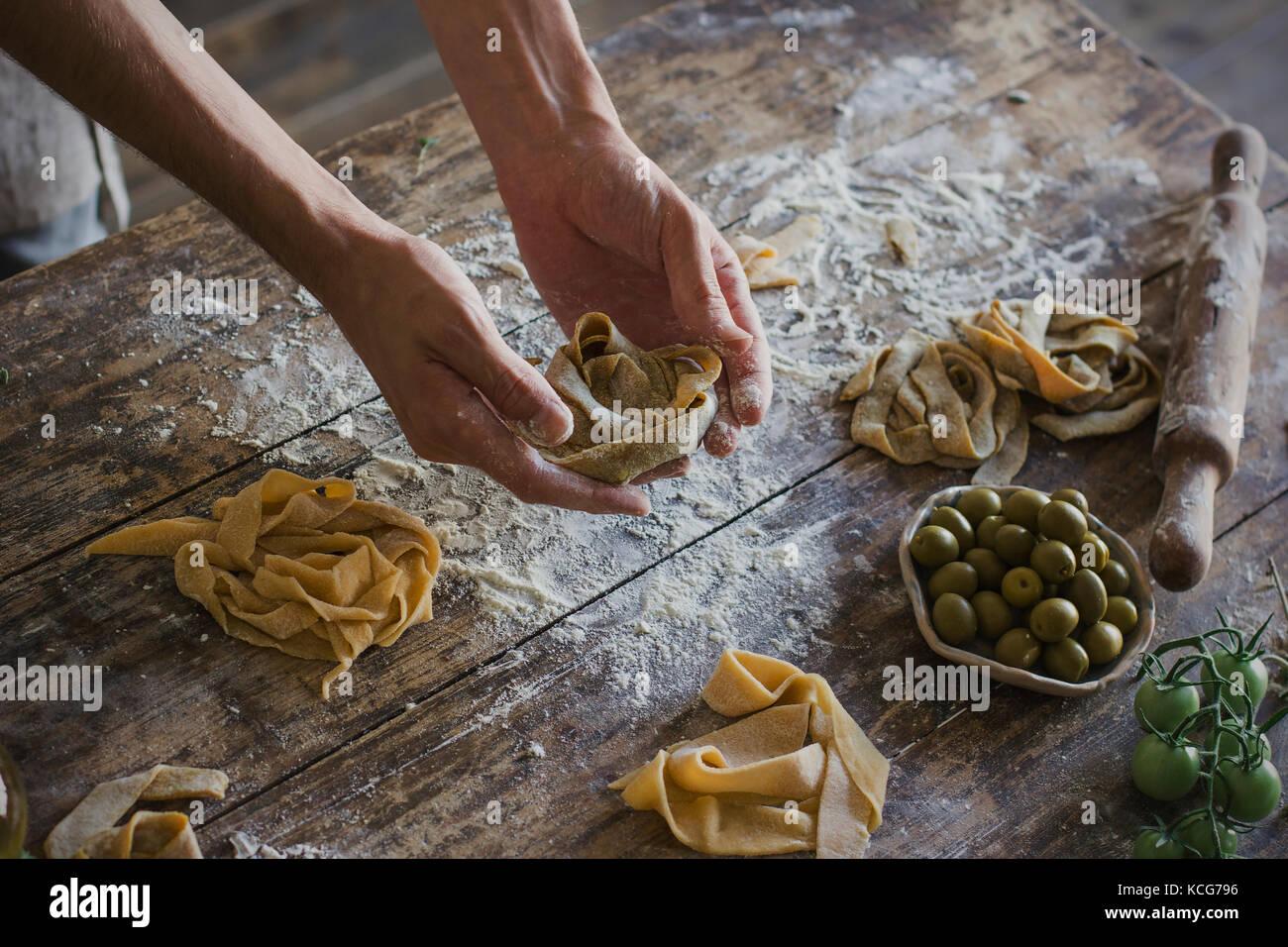 Il giovane uomo in grembiule rendendo la pasta fatta in casa Immagini Stock