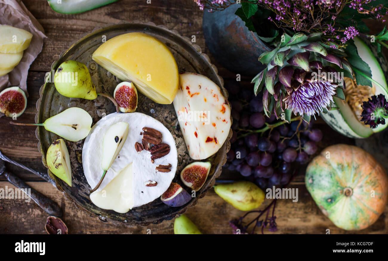 I vari formaggi e frutta fresca sullo sfondo di legno Immagini Stock