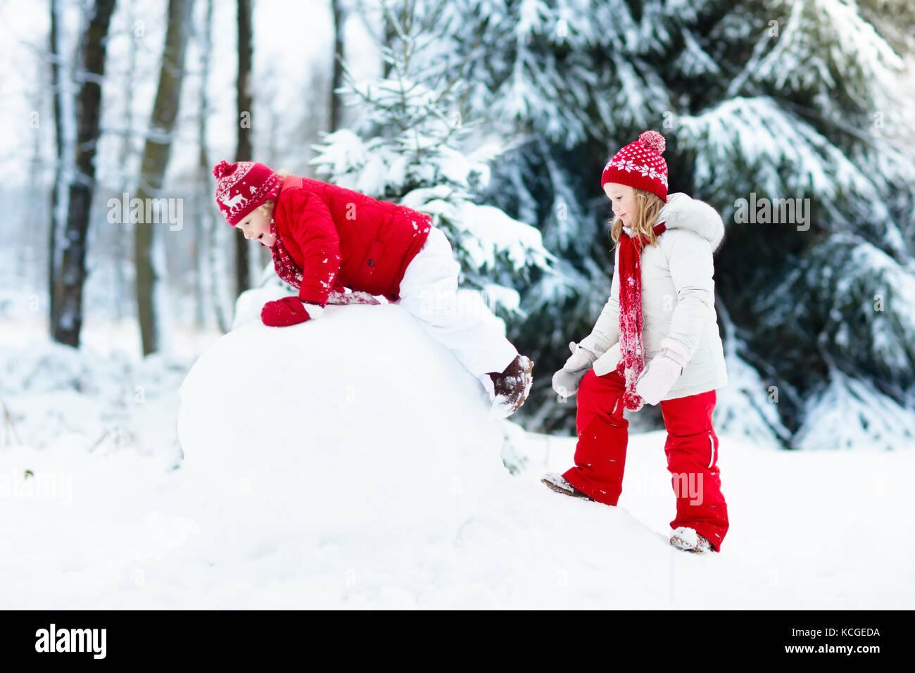 I bambini costruiscono pupazzo di neve. bambini edificio uomo di neve  giocando all aperto sul soleggiato inverno nevoso giorno. outdoor offre  divertimento ... b18b0d23bf4