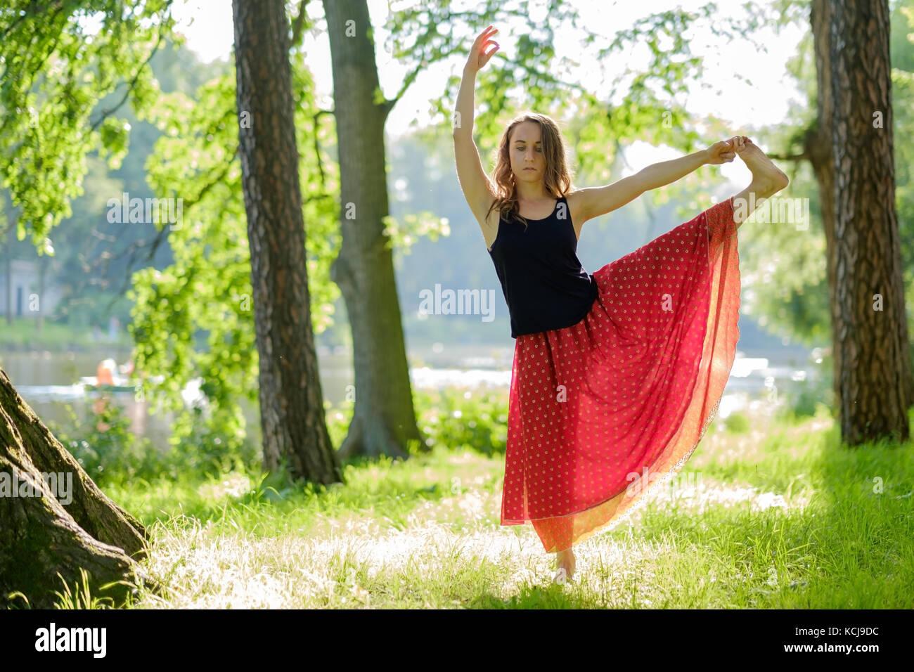 La donna caucasica nel mantello rosso equilibrio facendo yoga asana in estate park. Immagini Stock