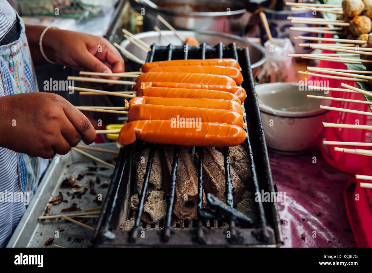 Un venditore ambulante rende tailandese alla griglia salsicce su spiedini al mercato warorot, Chiang Mai, Thailandia. Immagini Stock