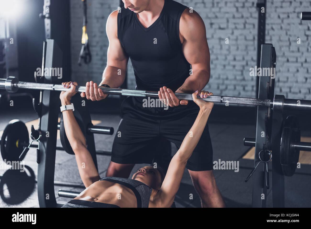 Trainer donna aiuta il sollevamento pesi Immagini Stock