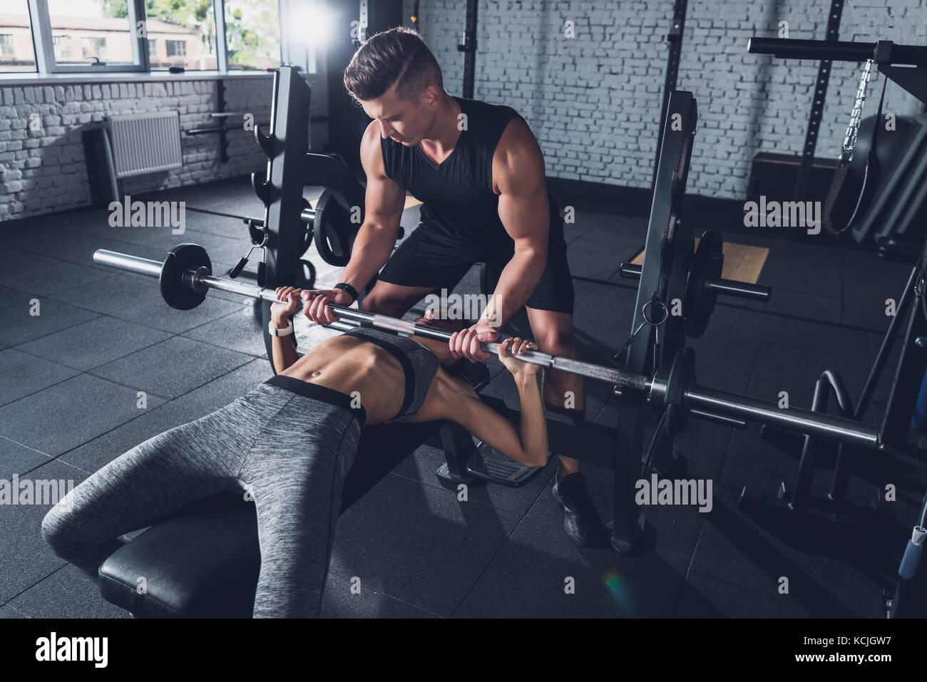 Trainer donna aiuta il sollevamento pesi Foto Stock