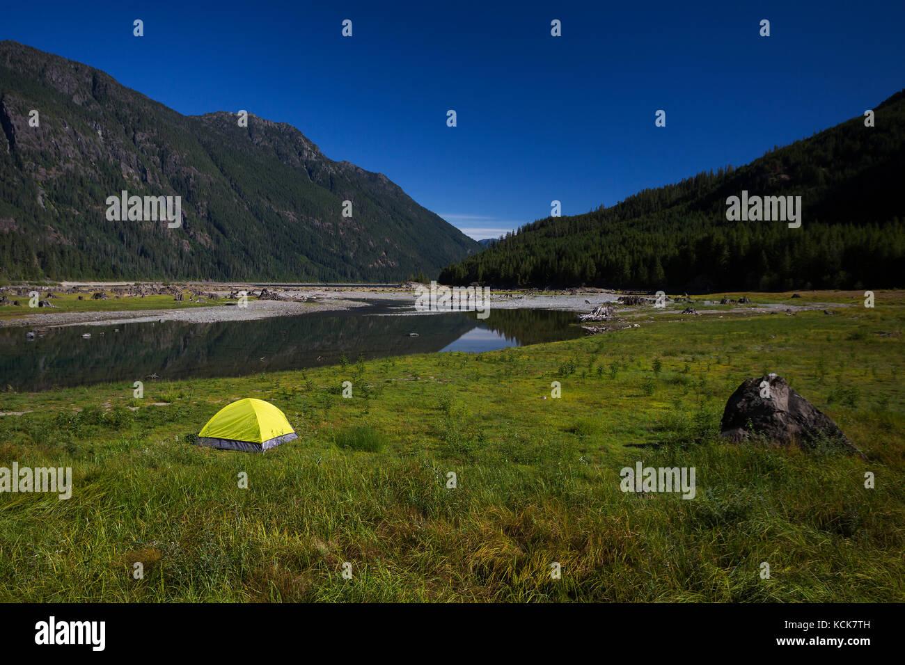 Un lone bright green tenda a capo del lago buttle in strathcona park offre contrasto stridente con un cielo azzurro, Immagini Stock