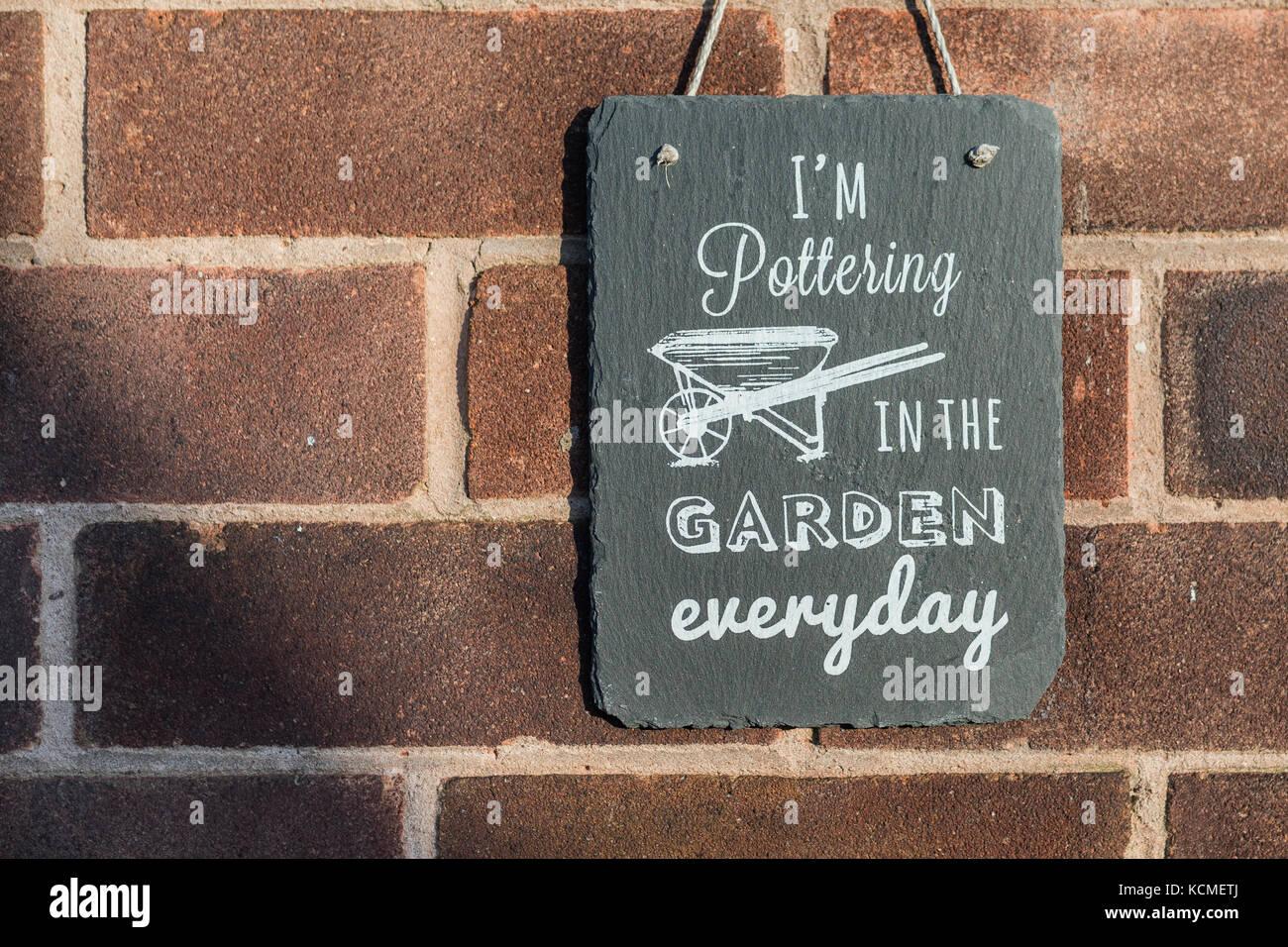 Sto pottering in giardino ogni giorno il giardino di ardesia segno appeso contro un muro di mattoni Immagini Stock