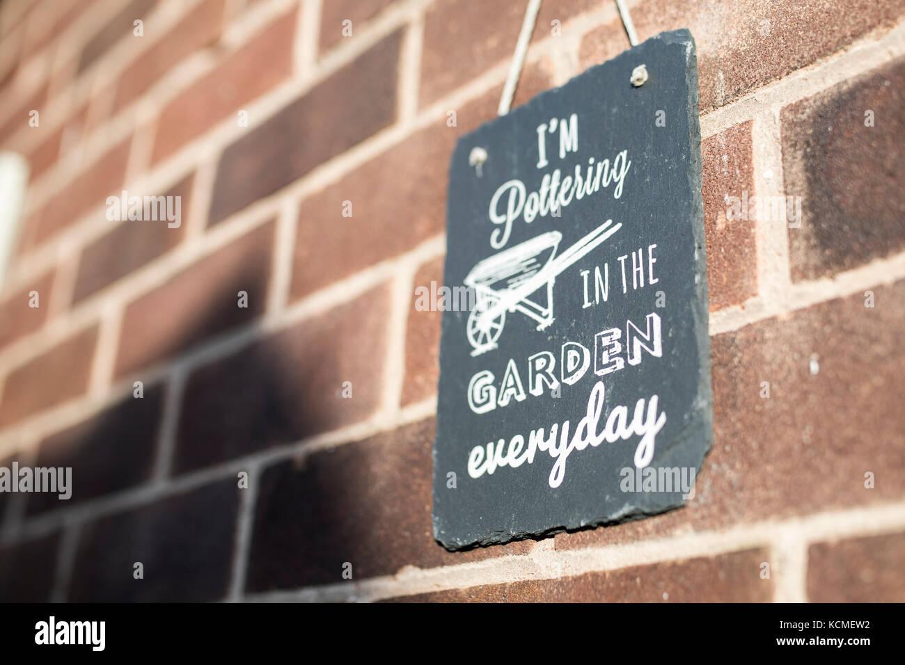 Sto pottering in giardino ogni giorno il giardino di ardesia segno contro un muro di mattoni Immagini Stock