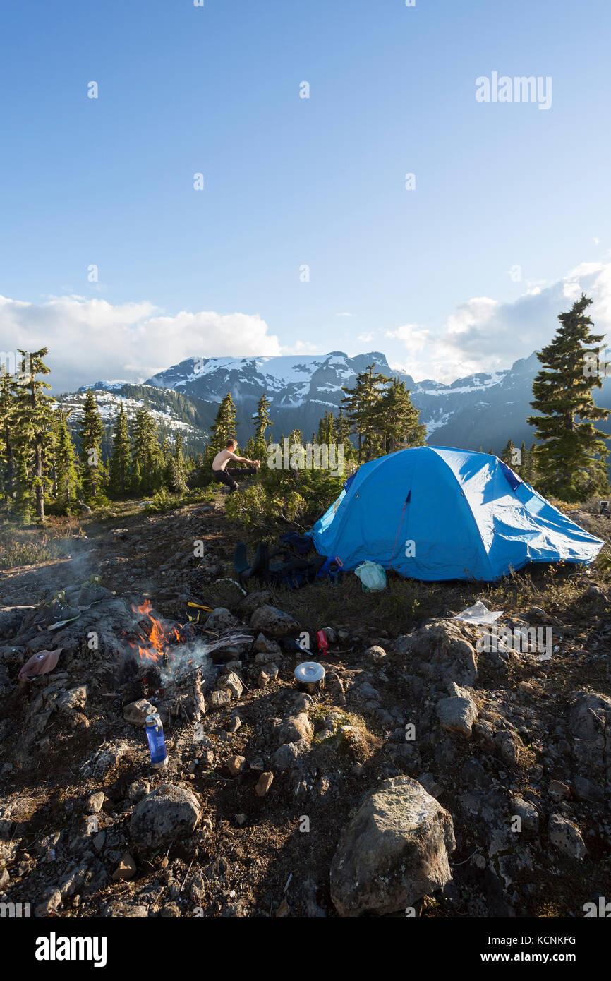 Un escursionista si allunga mentre il campeggio a lee altopiano, sull'isola di Vancouver, British Columbia, Immagini Stock