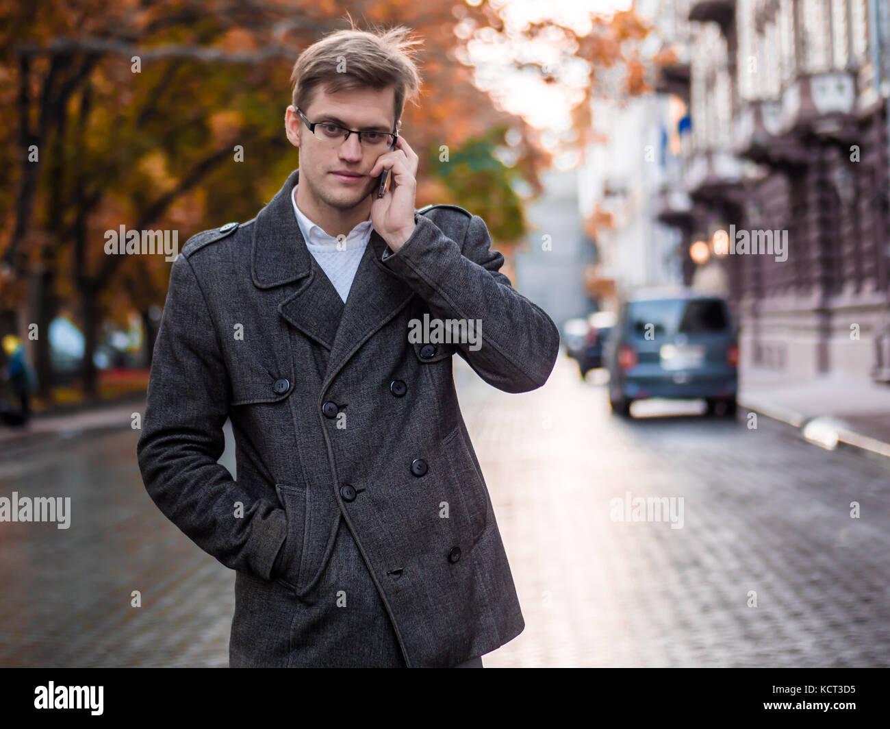 Giovane imprenditore bello parlando al telefono cellulare nella città. guy sentito buone notizie e lui è Immagini Stock