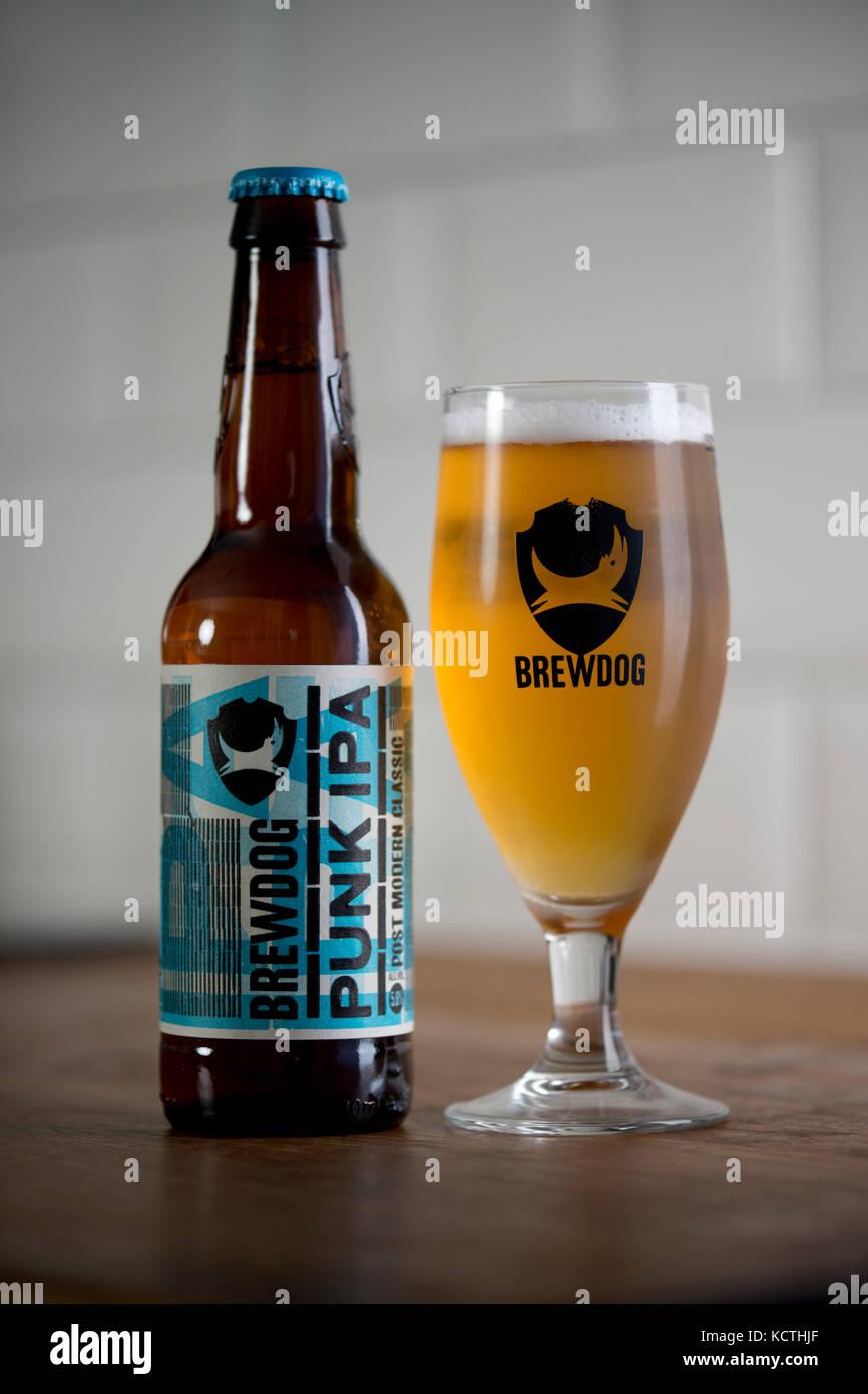Una bottiglia di BrewDog Punk IPA si trova accanto al marchio BrewDog bicchiere riempito di birra (solo uso editoriale). Immagini Stock