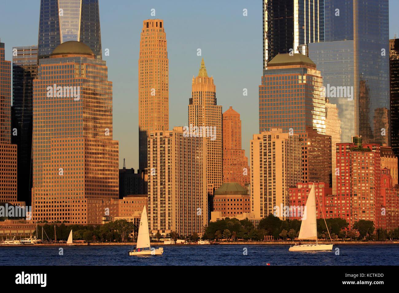 Skyline di Manhattan il quartiere finanziario con barche a vela nel fiume Hudson in primo piano sotto il tardo pomeriggio Immagini Stock