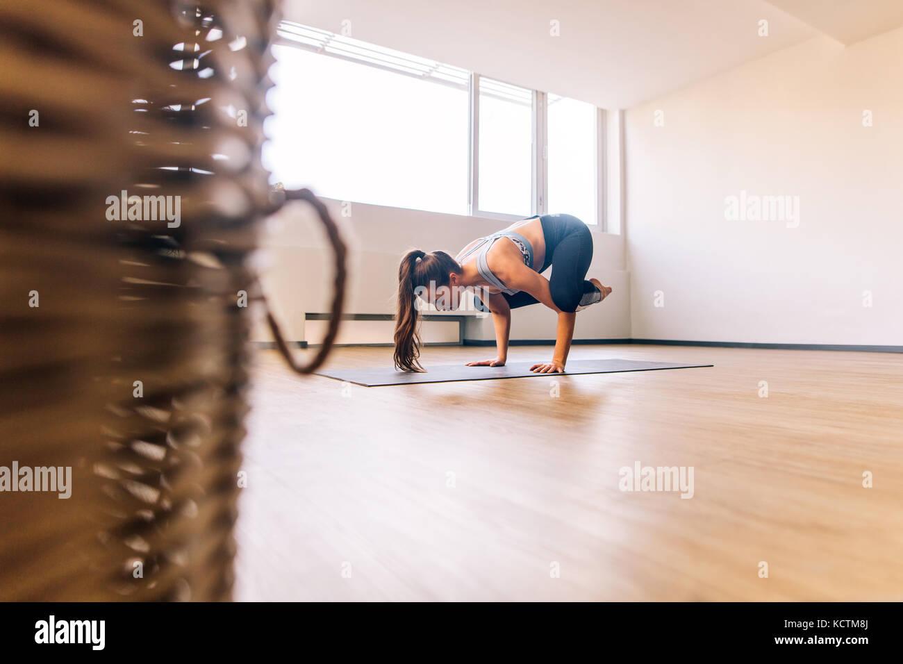 Donna in piedi sulle mani con i piedi sollevati gru facendo yoga posa. Donna Fitness praticando yoga Bakasana pongono Immagini Stock