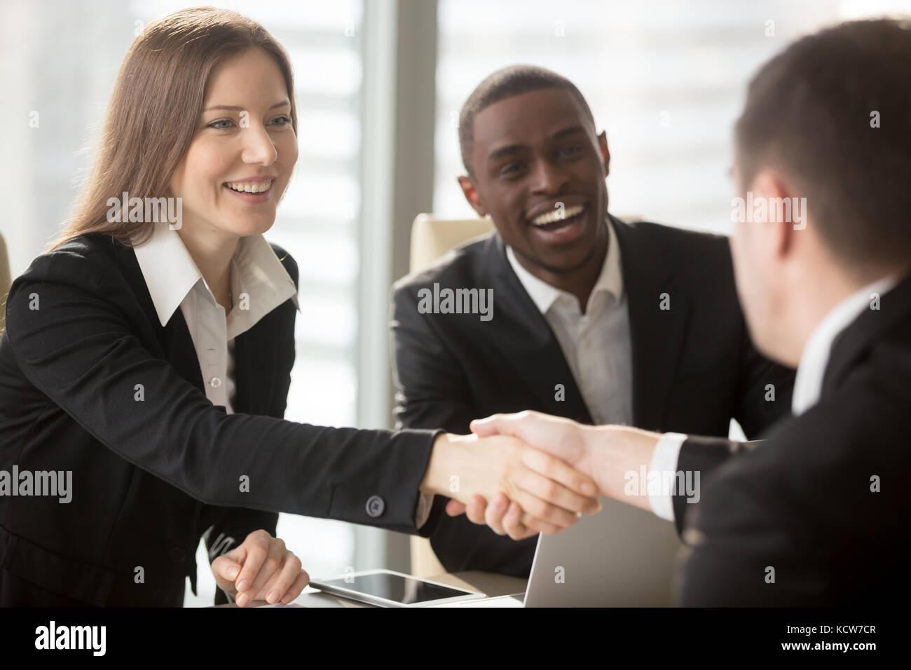 Bella imprenditrice sorridente con african partner americano agitando la mano e dare il benvenuto ai nuovi membri Immagini Stock