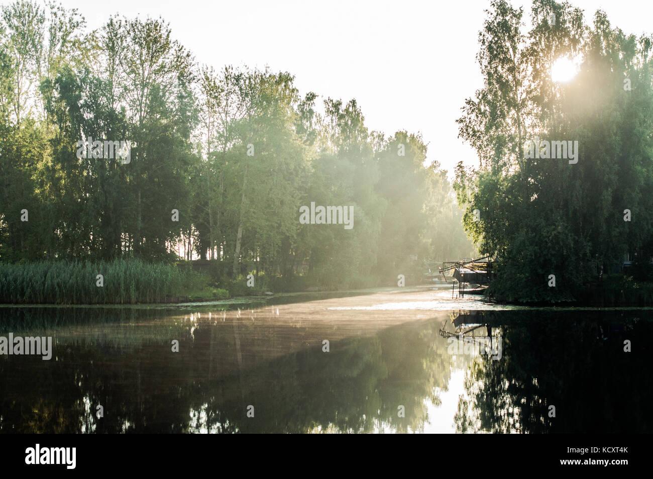 Raggi del sole attraverso i rami di betulla. Riflessioni sulla superficie del fiume. Piccolo porto. Immagini Stock