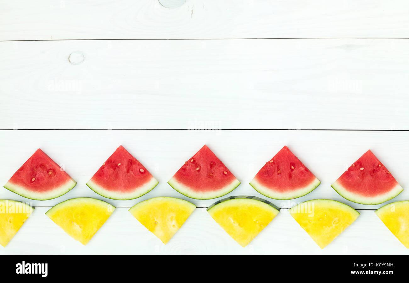 Rosso e Giallo le fette di anguria su bastoni di legno su un bianco sullo sfondo di legno. flat laico, vista dall'alto, Immagini Stock