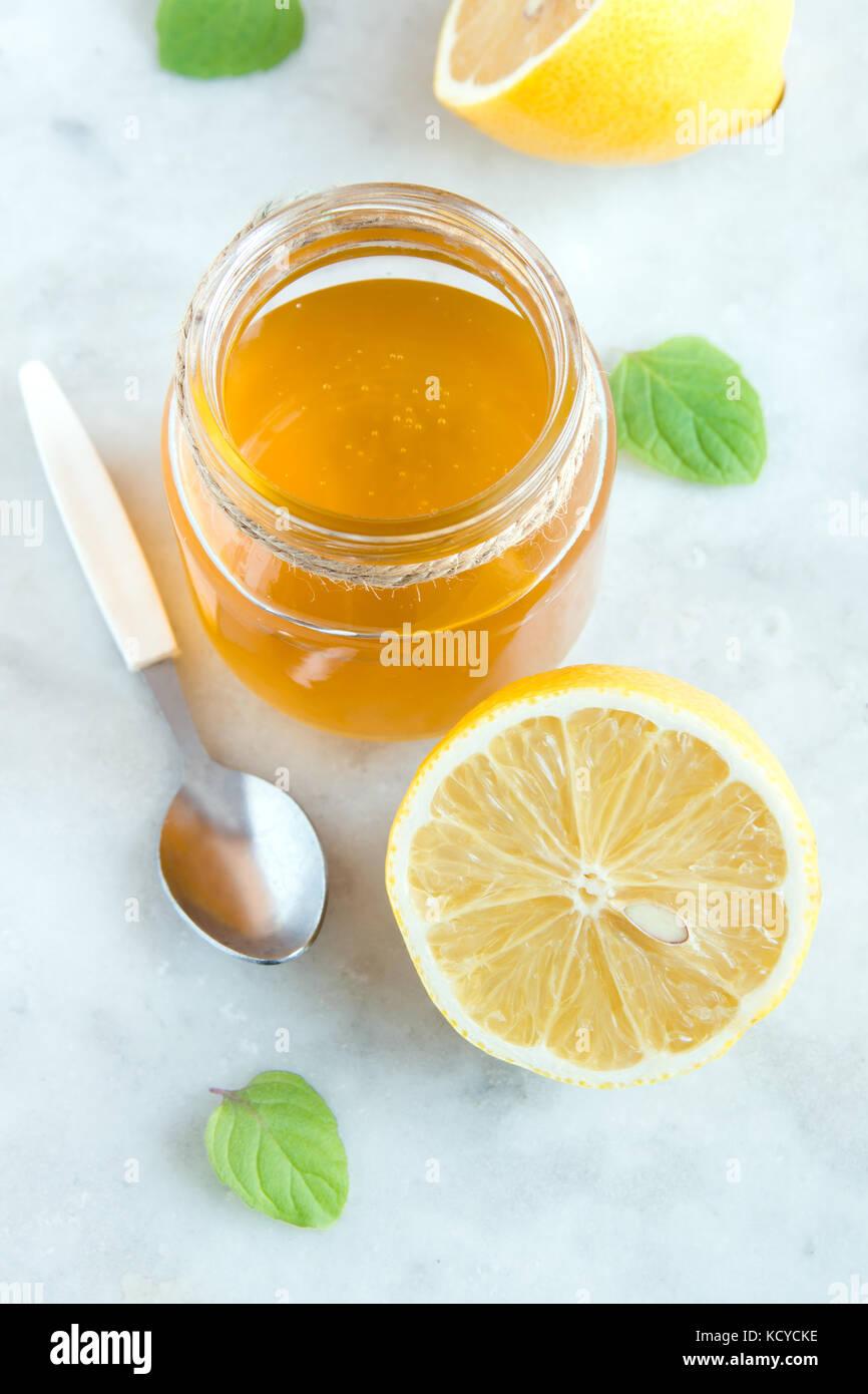 Limone e miele bianco su sfondo di pietra close up - sani prodotti organici per la medicina alternativa e di uno Immagini Stock
