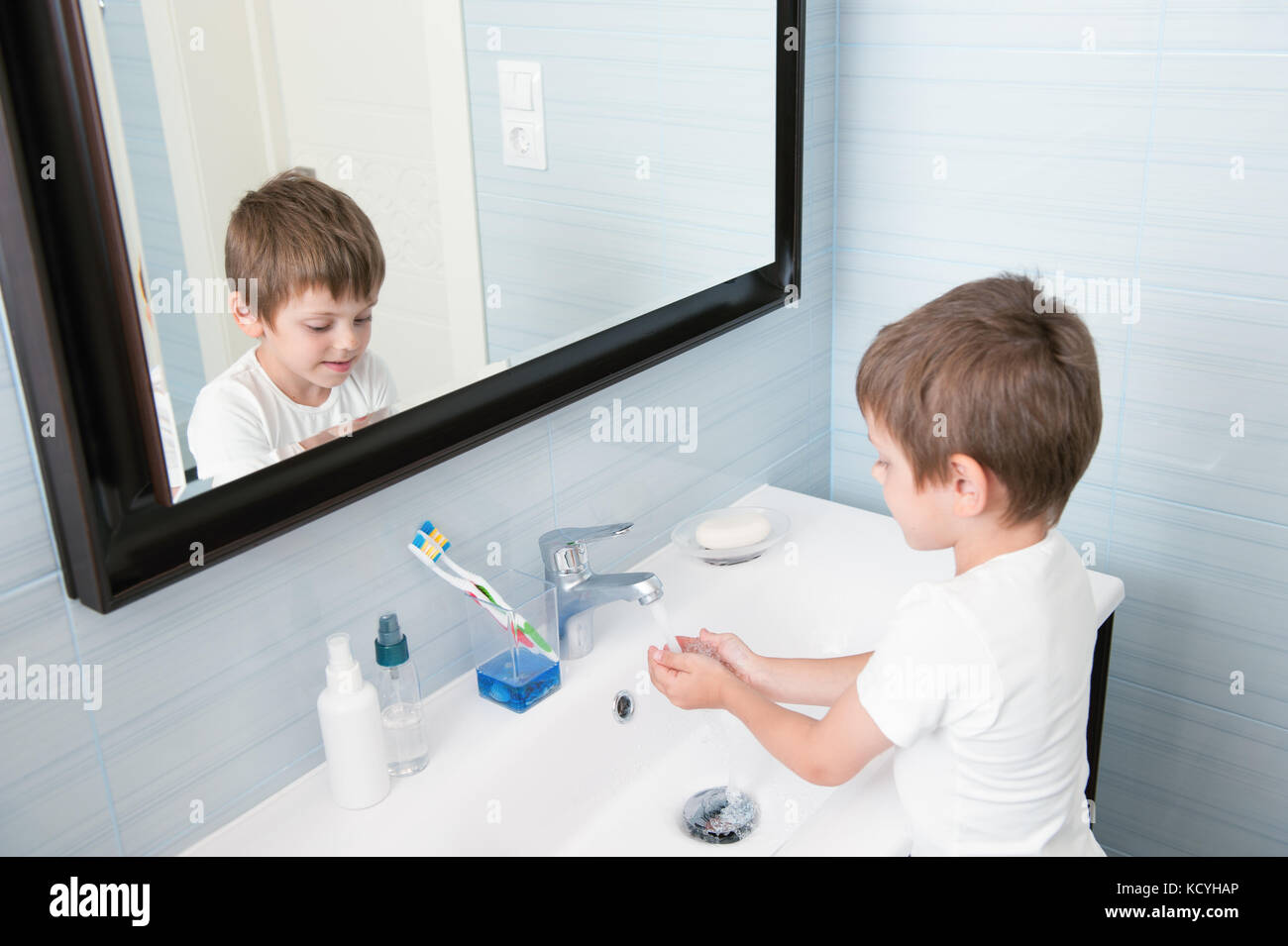 Splendido piccolo ragazzo lava le mani nel bagno di colore blu foto