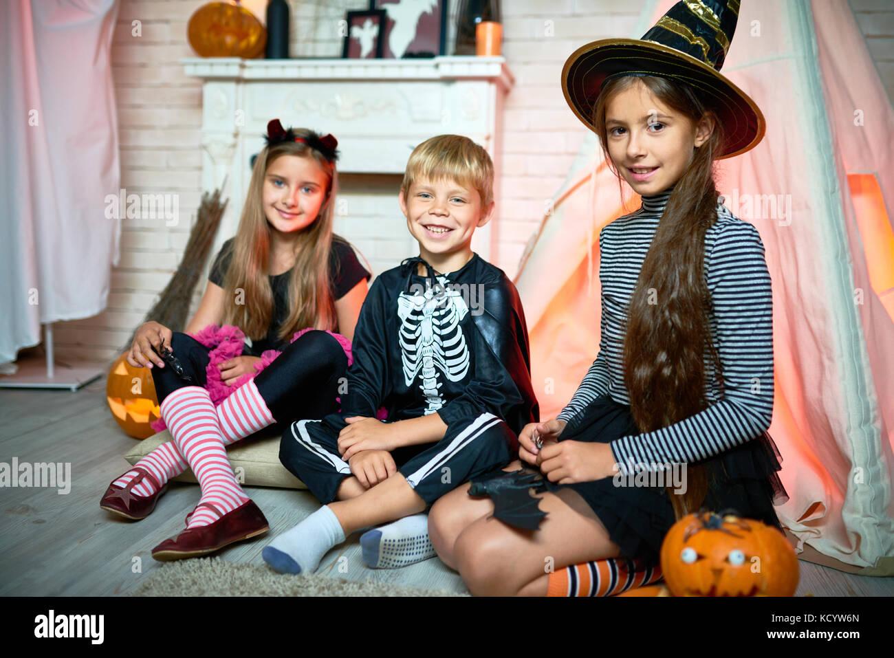 Ritratto di tre bambini che indossano costumi di Halloween in posa guardando la telecamera seduta sul pavimento Immagini Stock