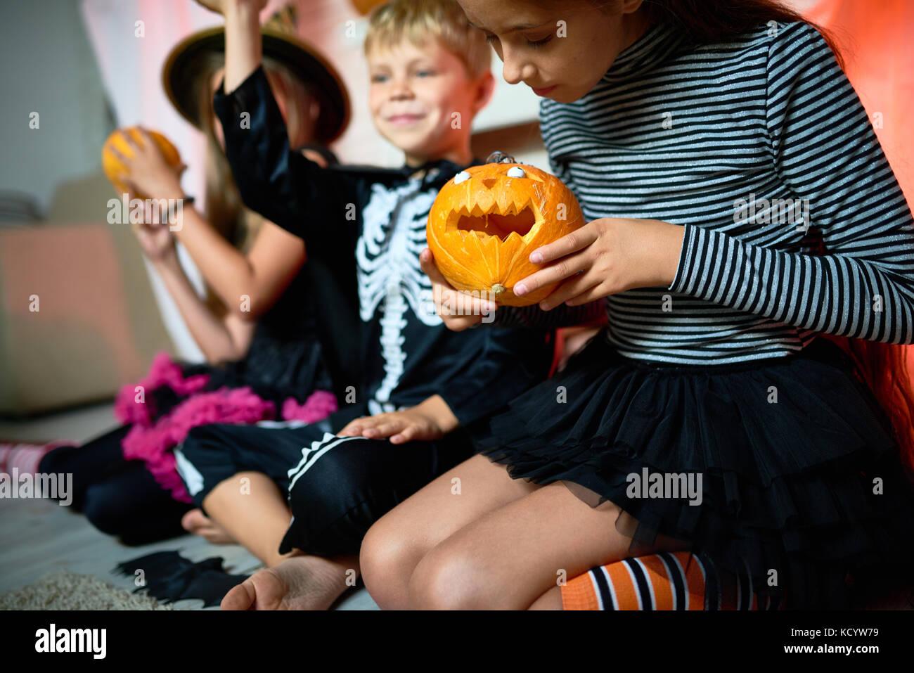 Closeup ritratto di tre bambini che indossano costumi di Halloween seduto sul pavimento in camera decorata, concentrarsi Immagini Stock