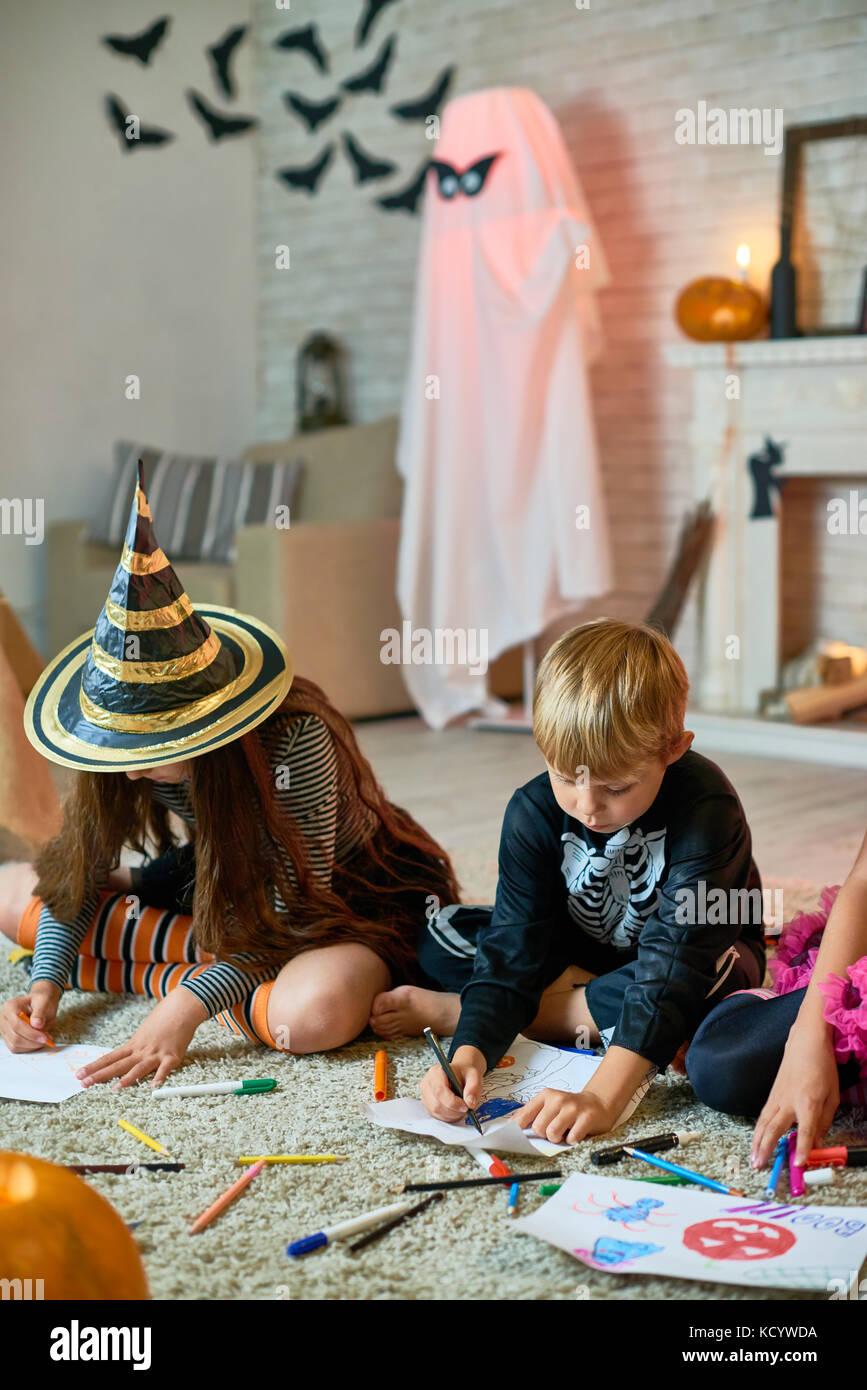 Ritratto di tre bambini che indossano costumi di Halloween disegno seduto sul pavimento decorato in studio Immagini Stock