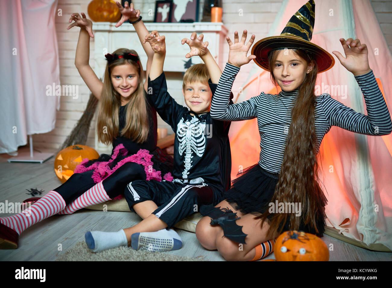Ritratto di gruppo di gioiosa dei bambini che indossano costumi di Halloween in posa per la fotografia mentre è Immagini Stock