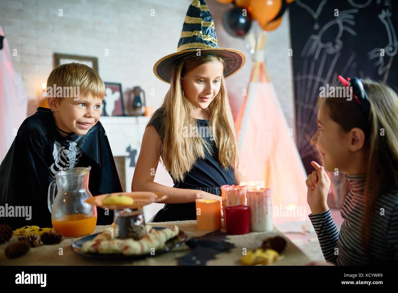 Vista di profilo di Pretty girl raccontando la storia spaventoso per i suoi piccoli amici mentre celebrare Halloween Immagini Stock