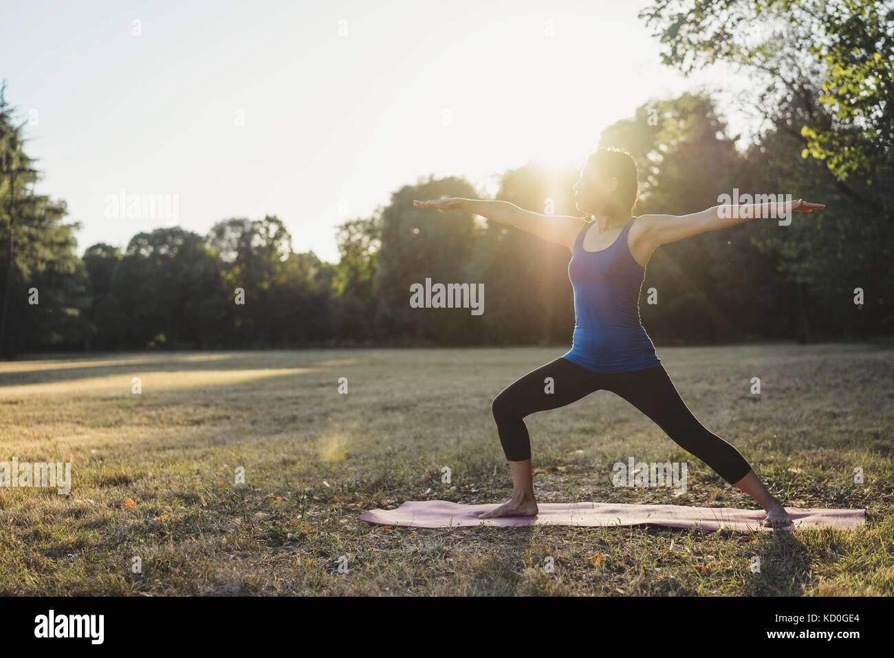 Donna matura nel parco, stando in piedi in posizione di yoga, braccia tese Foto Stock