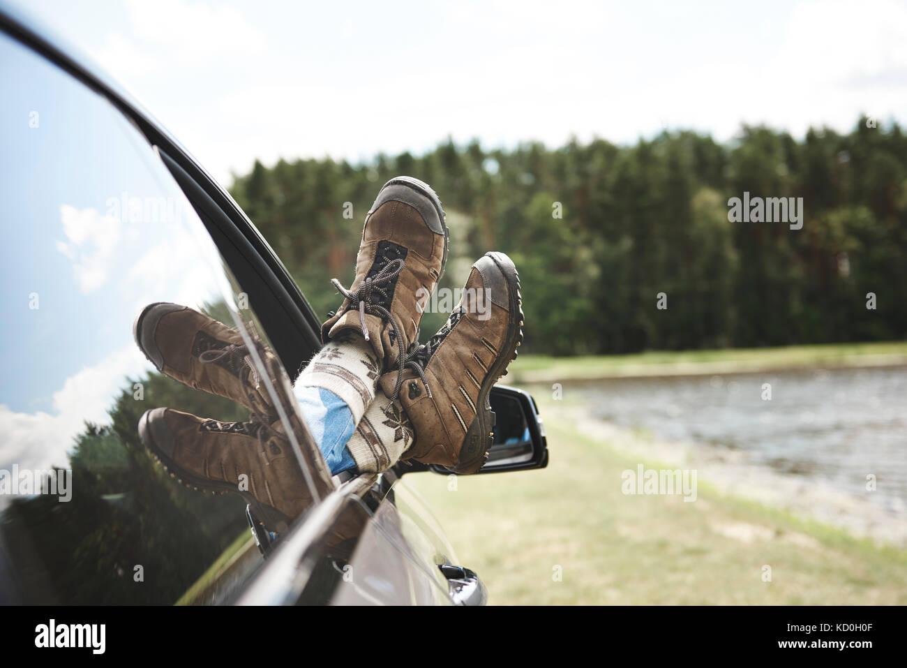Donna rilassante in auto, a piedi attraverso la finestra aperta, focus su piedi Immagini Stock