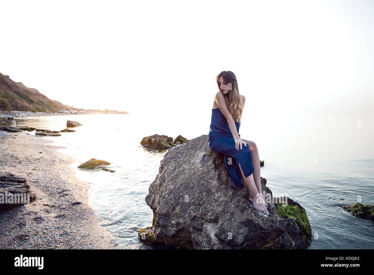 Giovane donna seduta sulla spiaggia rock, Odessa, Ucraina Foto Stock