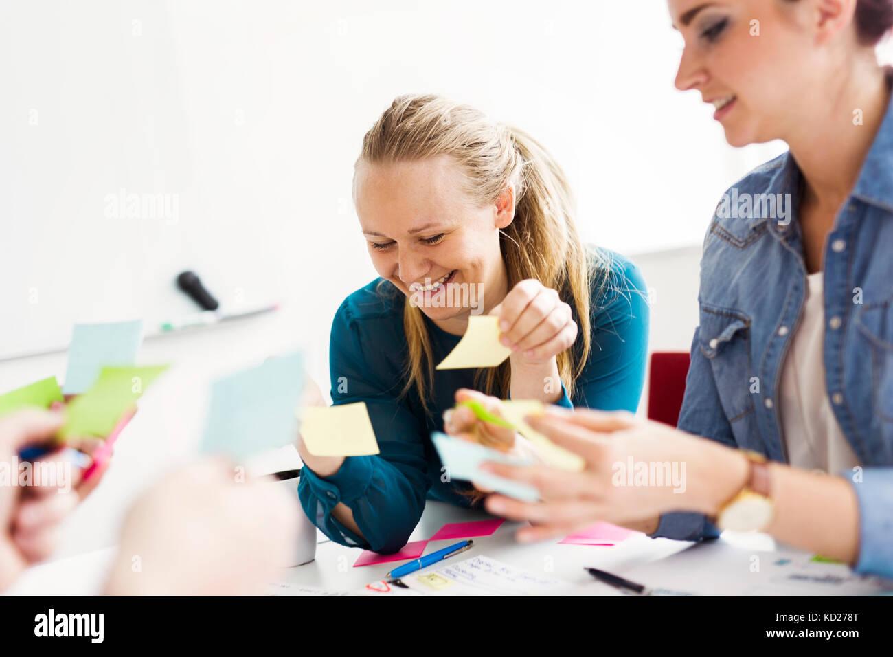 I colleghi utilizzando note adesive durante la riunione di affari Immagini Stock