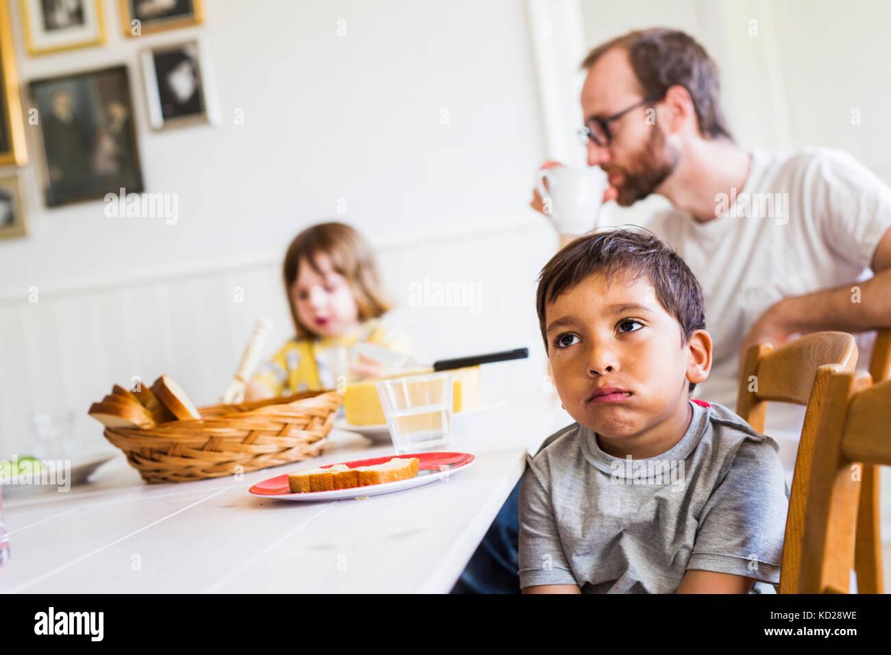 Padre e figli (2-3) in sala da pranzo Immagini Stock